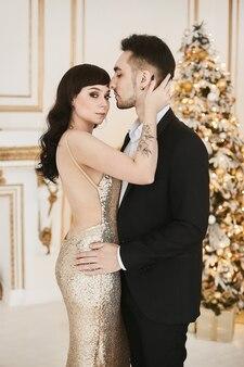 Сексуальная страстная пара вместе празднует рождество привлекательная женщина в золотом вечернем платье и хан ...