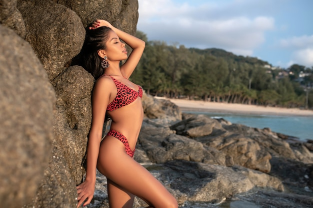 Sexy photo of brunette with long hair posing near rock in a bikini. concept of a beach photo shoot.