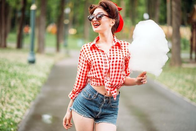 Сексуальная очаровательная девушка в солнцезащитных очках с сахарной ватой на палочке, ретро-американской моде. привлекательная женщина в стиле кинозвезды