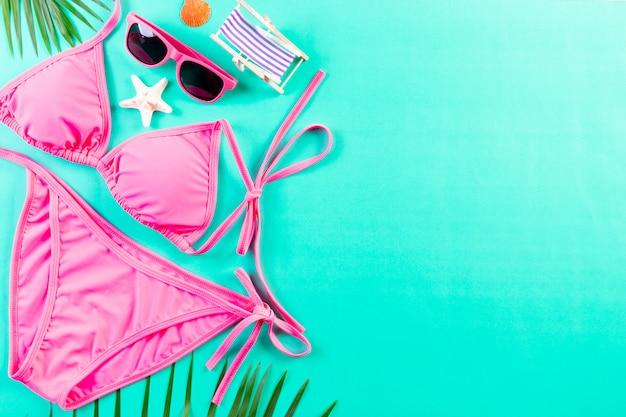 Сексуальное розовое бикини, солнцезащитные очки и пальмовые листья на светло-зеленом фоне. лето или отпуск концепции.