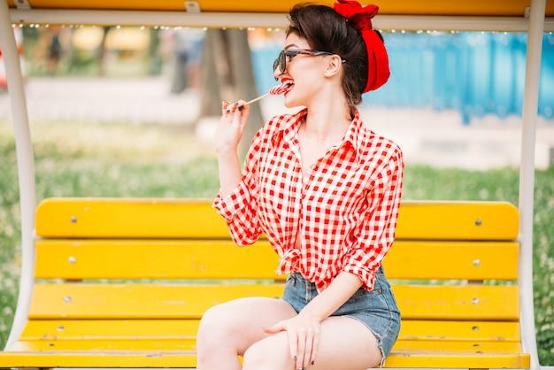 公園のベンチに座っているセクシーなピンナップガールと甘いロリポップ、レトロなアメリカンファッションをなめます。ピンアップスタイルの魅力的なモデル