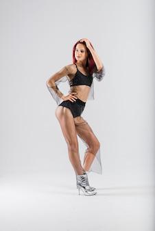 彼女の美しい体を見せているセクシーなポール赤毛ダンサー