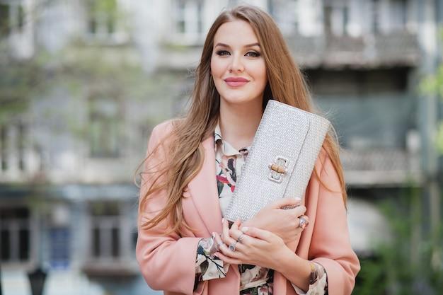 ピンクのコートで街を歩いて魅力的なスタイリッシュな笑顔の女性のセクシーな肖像画