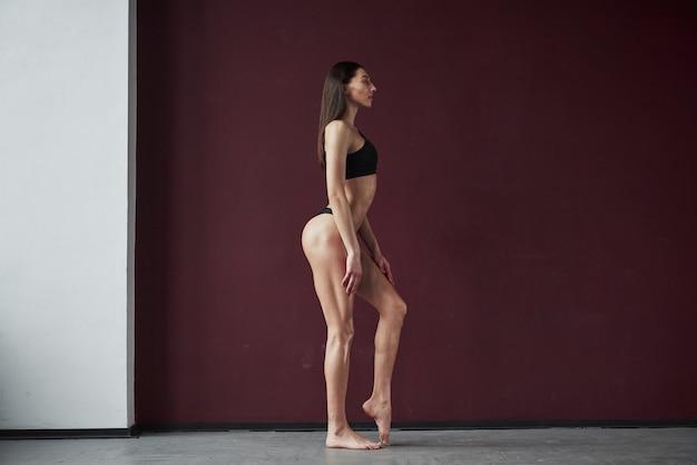 セクシーなポーズ。部屋に立っている素敵なフィットネスボディ形状を持つかなり若い女性