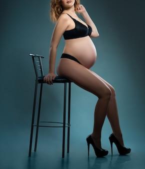 검은 가죽 재킷과 속옷에 스튜디오에서 섹시한 임신 한 여자