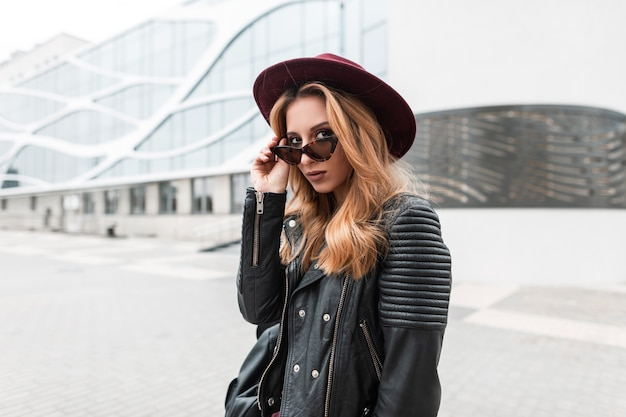검은 배낭 유행 가죽 재킷에 빈티지 모자에 선글라스에 섹시 꽤 젊은 힙 스터 여자