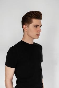 세련된 헤어스타일을 한 빈티지 보그 블랙 티셔츠를 입은 섹시한 젊은 남자가 방의 흰 벽 근처에 서 있습니다. 실내에서 세련된 캐주얼 옷을 입은 잘 생긴 남자 패션 모델. 스튜디오 프로필 사진입니다.