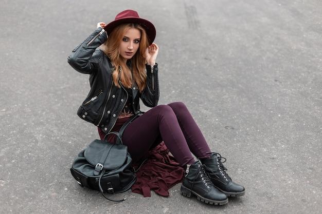 유행 배낭과 유행 바지에 가죽 재킷에 보라색 모자에 섹시한 빨간 머리 젊은 여자