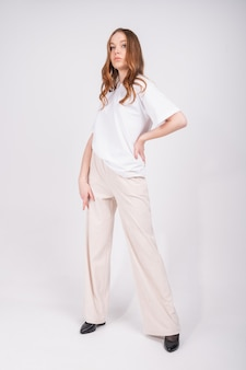 Sexy redhead woman wear white t-shirt and light trousers, full length portrait isolated on white wall. spring summer fashion trend. fashion outfit.
