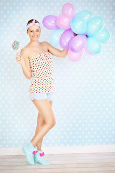 A sexy retro woman posing with a lollipop and balloons over white and blue dotted background