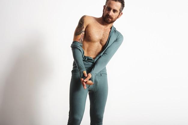 Atleta barbuto strappato sexy con il tatuaggio che si spoglia della sua usura termica dello strato di base, isolato su bianco