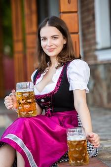 ビールジョッキを保持しているバイエルンのドレスでセクシーなロシアの女性