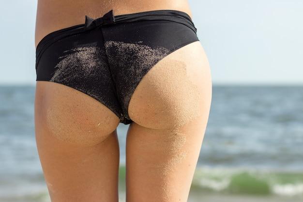 Sexy sandy woman buttocks on tropical beach background near ocean.