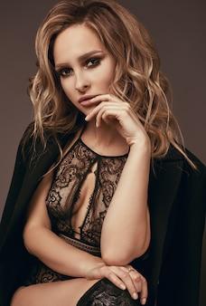 속옷과 검은 코트에 섹시한 매혹적인 금발 소녀