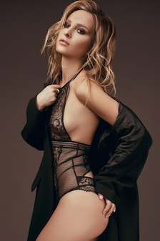 Sexy seductive blonde girl in underwear and black coat