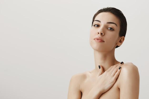 裸で立って、肩に優しく触れるセクシーな官能的な女性