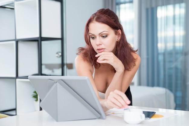 Сексуальная серьезная бизнесмен, используя цифровой планшет Бесплатные Фотографии