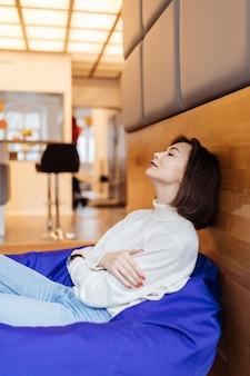 섹시한 쇼트 헤어 모델은 휴식을 가지고 집에서 파란색 가방 의자에 앉아 매일 낮잠을