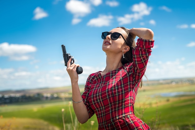 Sexy slender girl in a red dress holding a gun at nature, summer lifestyle