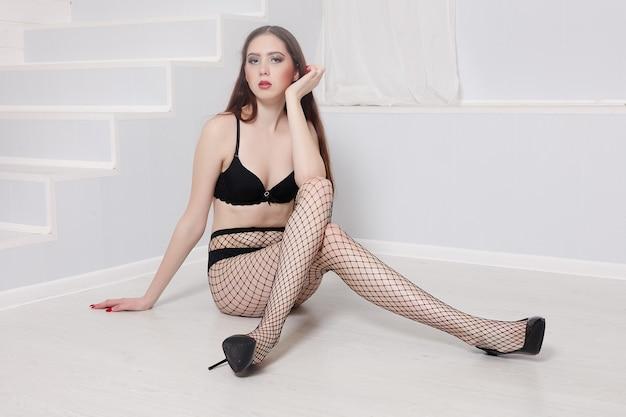 パンストメッシュと白い背景の上の黒いレースのパンティーで美しい脚を持つセクシーなほっそりした女の子