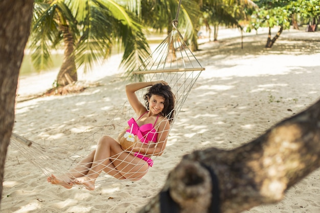 Sexy slim girl enjoys relaxing in a hammock on the shore of a tropical paradise island.