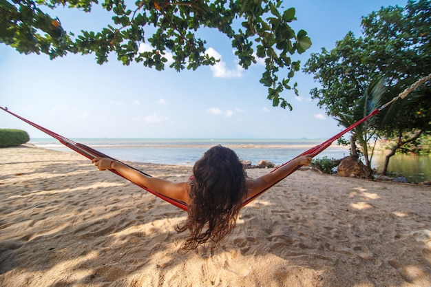 Сексуальная стройная девушка любит отдыхать в гамаке на берегу тропического райского острова.