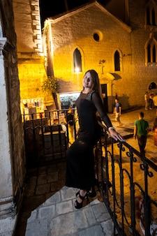 夜の古いヨーロッパの通りでポーズをとって長い黒のドレスを着たセクシーなスリムな女性