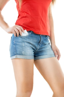 Sexy slim woman in jeans shorts posing with packed condom
