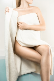 Sexy slim woman sitting on side of bath and covering in towel