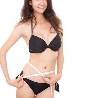 Сексуальная стройная молодая женщина, измеряющая свое идеальное тело на белом фоне, на диете