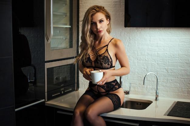 집에서 테이블에 앉아있는 동안 커피를 마시는 속옷에 섹시한 웃는 소녀