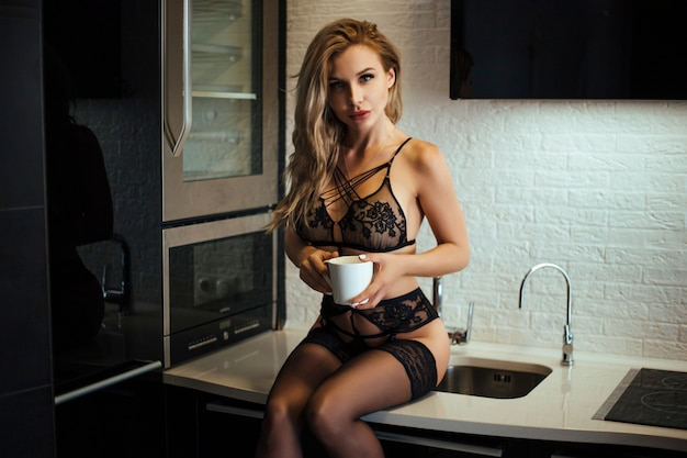 Sexy smiling girl in underwear drinking coffee while sitting on table at home
