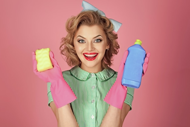 Sexy smiling housekeeper in uniform with clean spray, sponge.