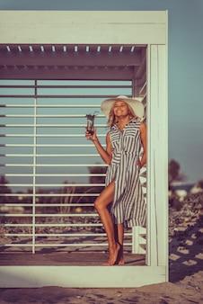 Сексуальная улыбающаяся женщина в длинном льняном платье и шляпе с загорелой кожей и идеальной фигурой стоит рядом с пляжем