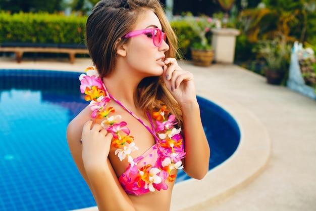 Donna sorridente sexy in vacanza estiva divertendosi in piscina indossando bikini e occhiali da sole rosa, fiori tropicali alle hawaii, colorato stile moda estiva
