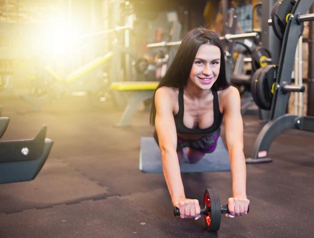 체육관에서 복근 롤러 운동을 하 고 스포츠에 섹시 한 스포츠 갈색 머리.