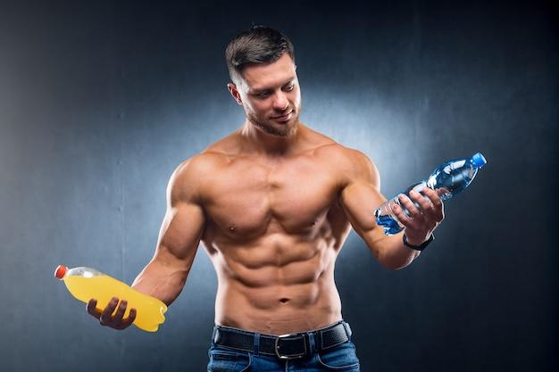 Сексуальный спортсмен держит бутылку воды и соды.