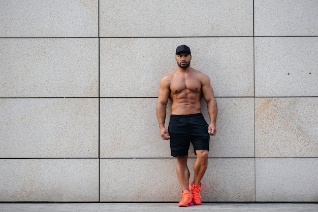 Sexy sportsman stands topless near the wall. fitness, bodybuilding