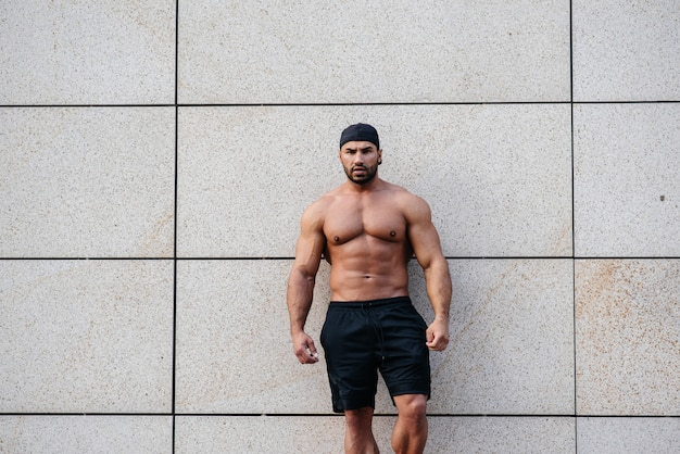 Sexy sportsman stands topless near the wall. fitness, bodybuilding.
