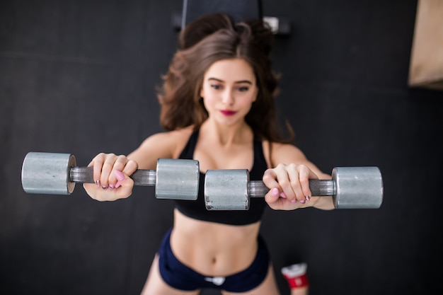 Sexy sporty muscular young woman working out with two metallic dumbbells