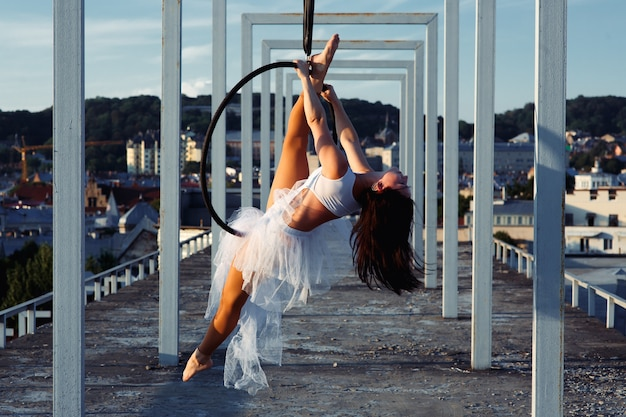 Sexy strong dancer performing on aerial hoop on rooftop
