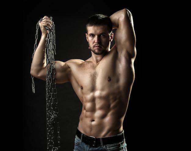 근육질 몸매가 손에 밧줄을 잡고 섹시한 강한 젊은이