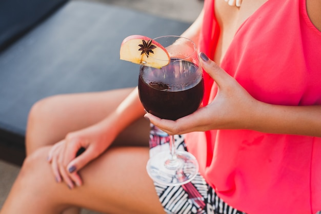 Sexy stylish woman in fashion party outfit on summer vacation close up hand with glass of cocktail having fun on pool