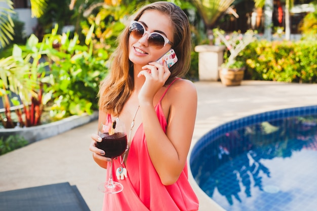 Sexy stylish woman in fashion party outfit on summer vacation with glass of cocktail having fun on pool talking on phone