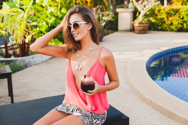 Sexy stylish woman in fashion party outfit on summer vacation with glass of cocktail having fun on pool
