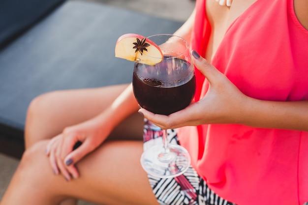 Сексуальная стильная женщина в модном наряде на летних каникулах закрывает руку с бокалом коктейля, развлекаясь в бассейне