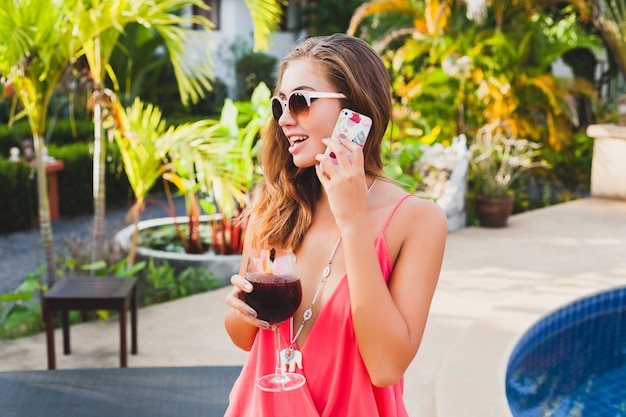 電話で話しているプールで楽しんでいるカクテルのガラスと夏休みのファッションパーティーの衣装でセクシーなスタイリッシュな女性