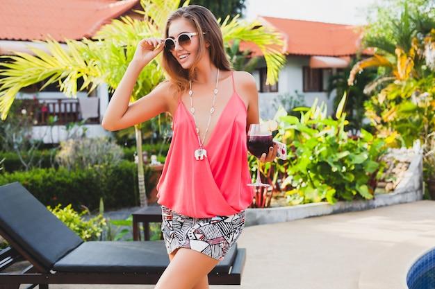 Сексуальная стильная женщина в модном наряде на летних каникулах с бокалом коктейля, весело проводящим время в бассейне