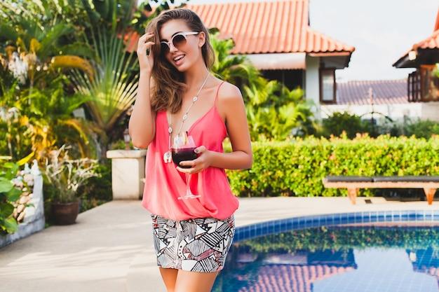 プールで楽しんでいるカクテルのガラスと夏休みのファッションパーティーの衣装でセクシーなスタイリッシュな女性