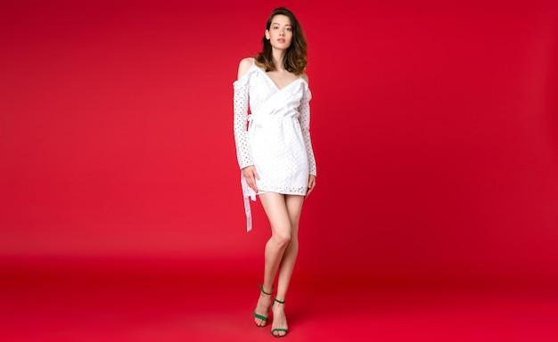 赤いスタジオでポーズ夏のファッション傾向の白いドレスでセクシーなスタイリッシュな女性